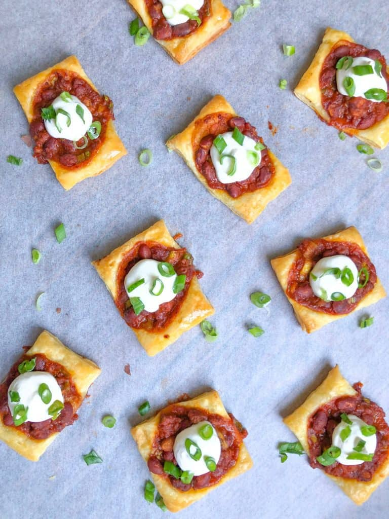puff pastry chili bites on a baking sheet with sour cream on top.