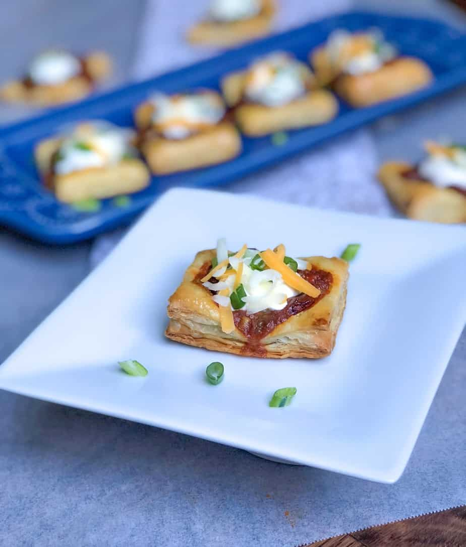 hormel chili on top of puff pastry square on a plate with sour cream
