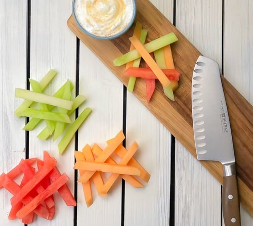 fruit fries cut into sticks on cutting board with knife