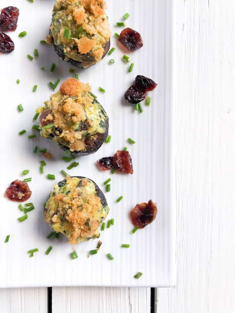 Easy mini portobello stuffed mushrooms with cream cheese and kale (or spinach) and craisins! They are vegetarian topped with panko breadcrumbs and chives. They are a simple baked appetizer perfect for any party!