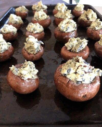 mini portobello mushrooms on a baking sheet stuffed with cream cheese kale and craisins