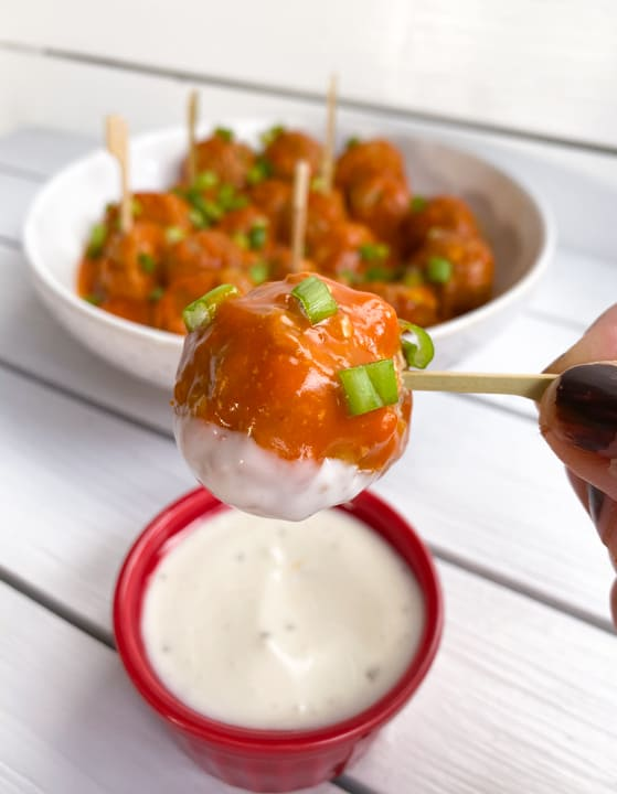 spicy and sweet buffalo turkey meatballs on a skewer dipped in blue cheese dressing