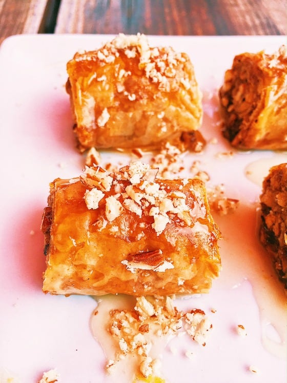 Easy traditional Greek rolled baklava bites! Homemade from scratch with honey, walnuts and phyllo dough. Learn how to make with step by step instructions!