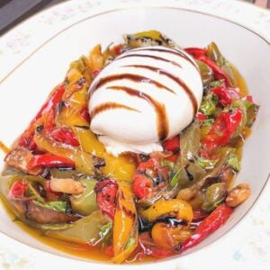 Italian burrata cheese appetizer over roasted peppers in a dish