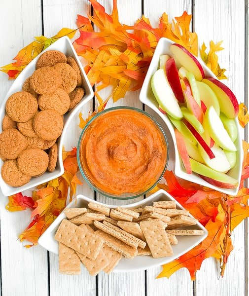 pumpkin puree dip in a bowl with gingersnaps, apples and graham crackers