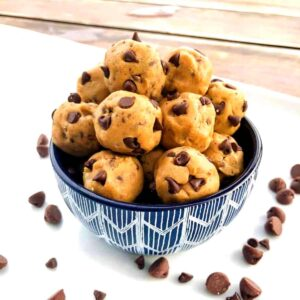 Edible chocolate chip cookie dough balls stacked in a bowl with chips sprinkled around.