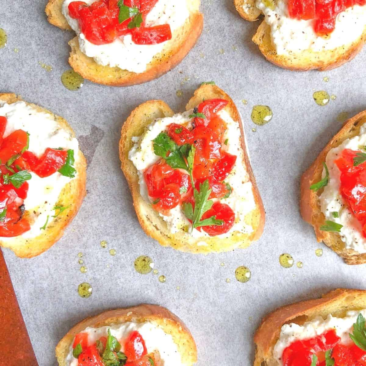 crostini appetizer on a plate with ricotta cheese and peppers