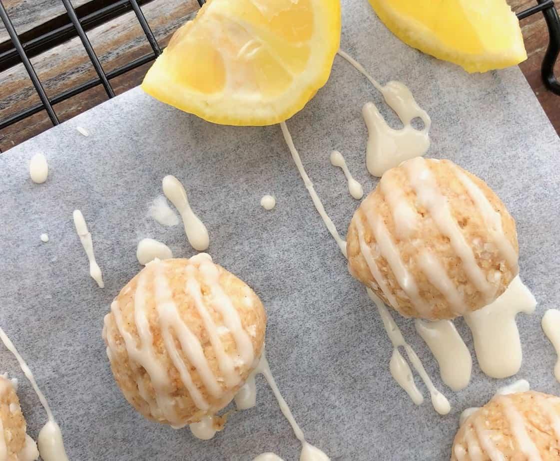lemon cream cheese truffles with lemon drizzle on parchment paper.
