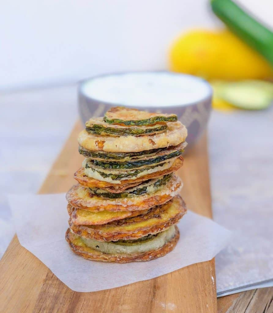 homemade crispy zucchini chips in a tall tower on cutting board
