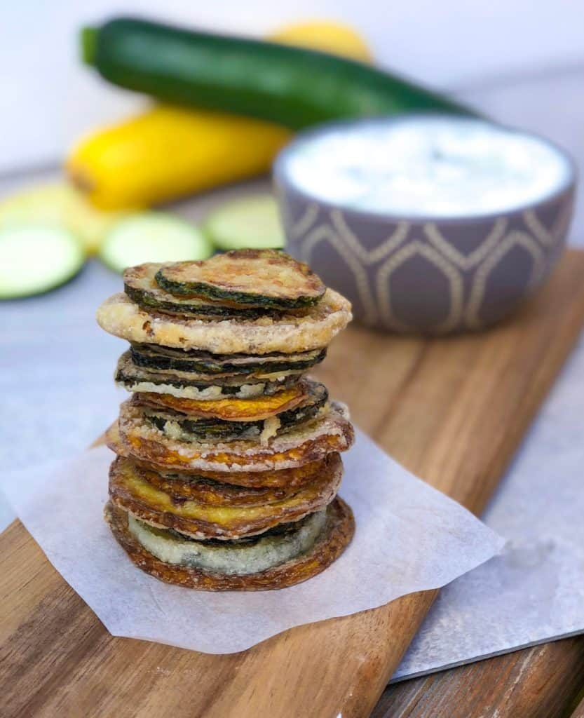 fried zucchini chips stacked on a cutting board