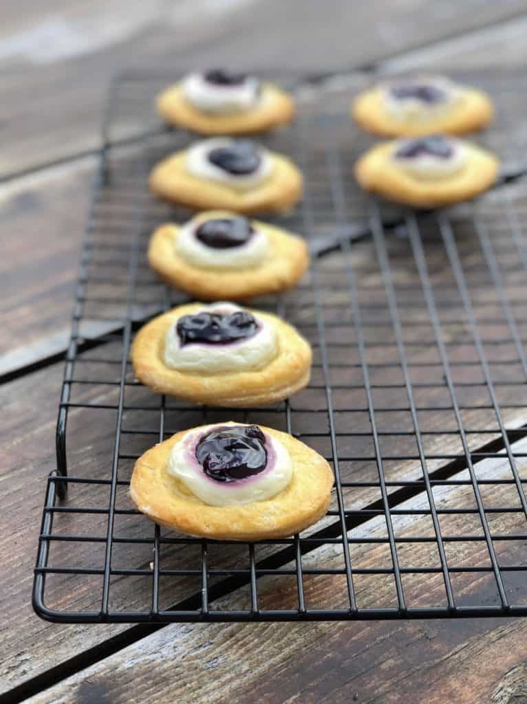 crescent dough rounds with blueberry and cream cheese on a drying rack