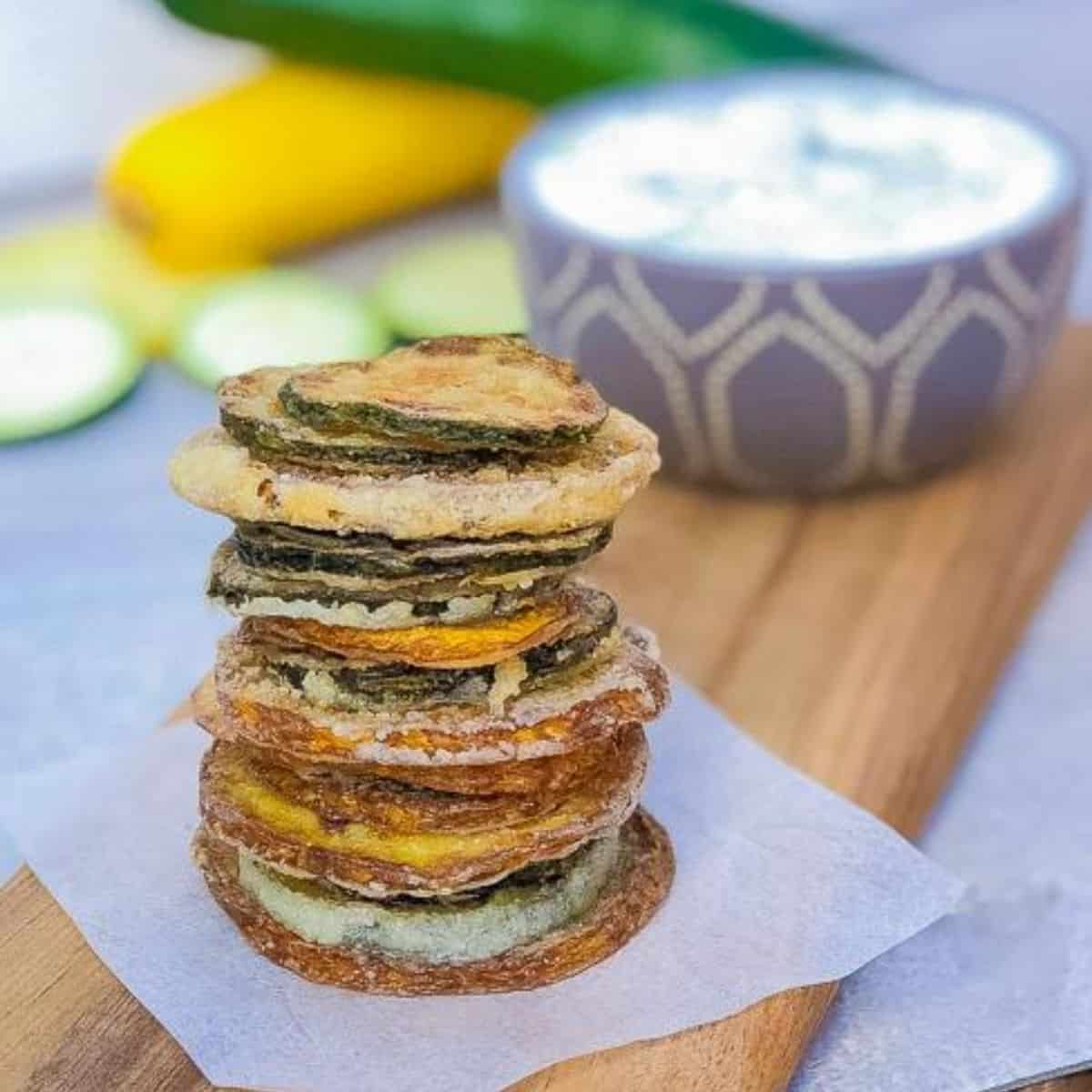 pan fried zucchini chips in a stack with tzatzik sauce