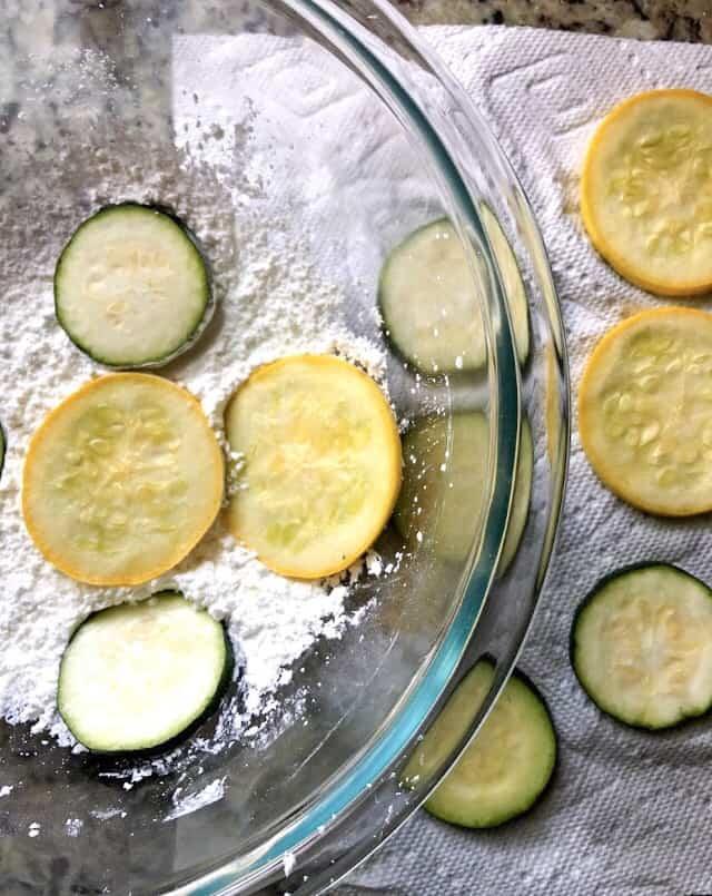 zucchini chips dredged in cornstarch in a bowl