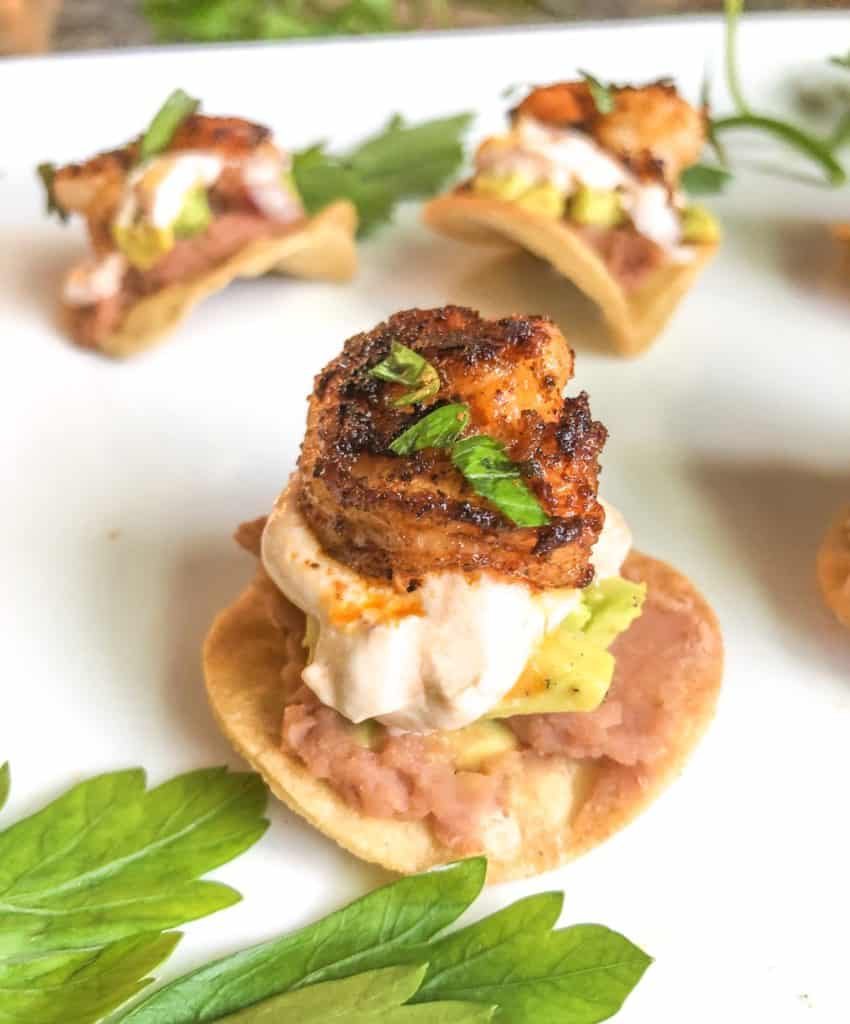 mini shrimp canapes with sour cream and bean paste on a white plate
