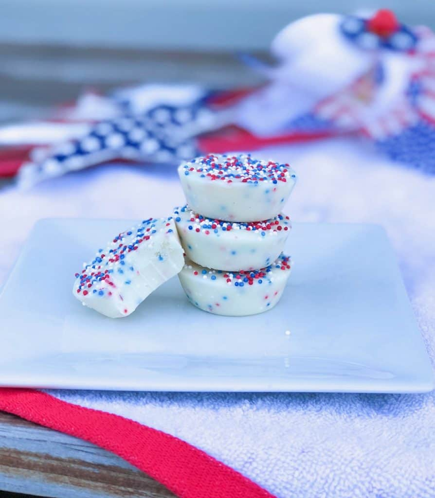 vanilla fudge bites without condensed milk stacked on a plate with red white and blue sprinkles