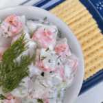 crab salad with greek yogurt in a bowl with fresh dill and crackers on the side