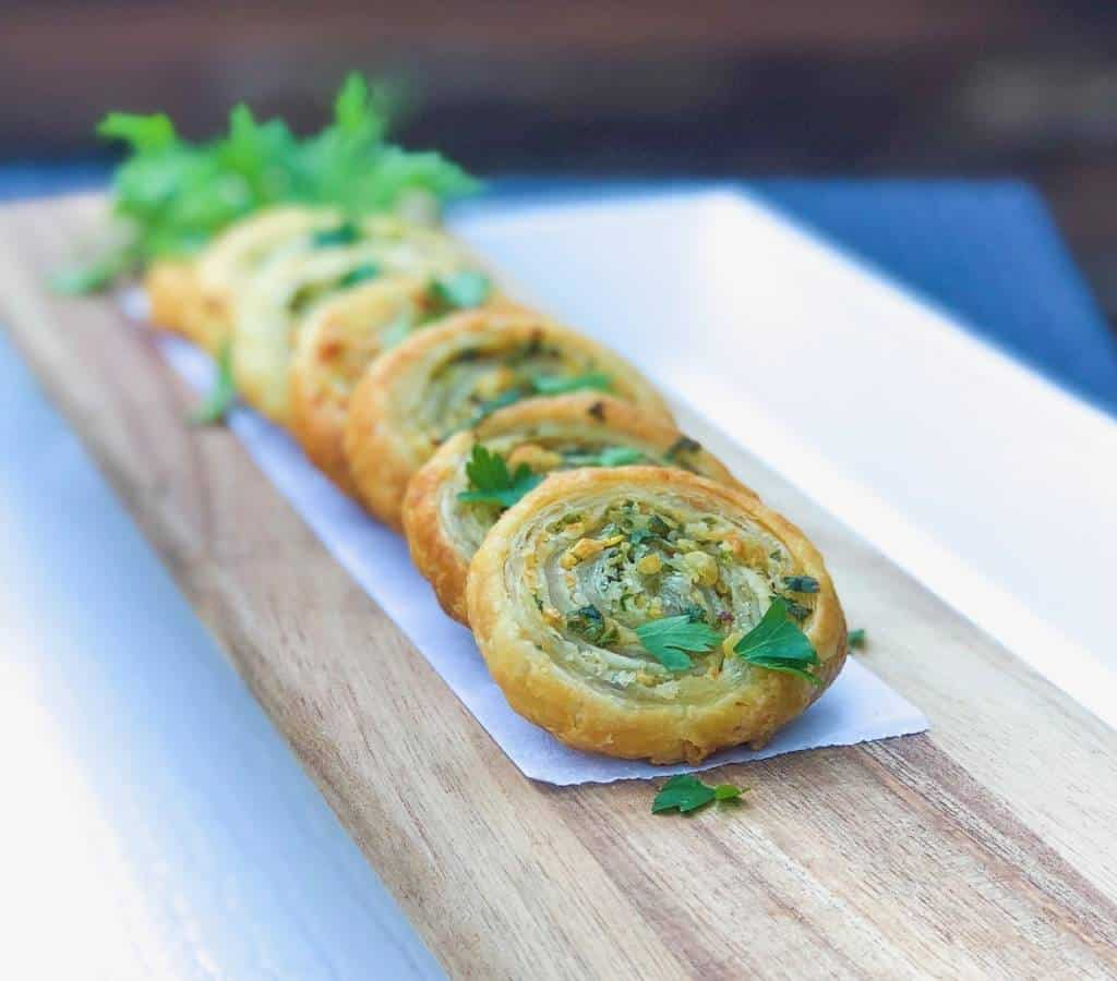 puff pastry pinwheels with parsley on top.