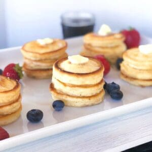 stacks of mini pancakes with butter on top and berries around