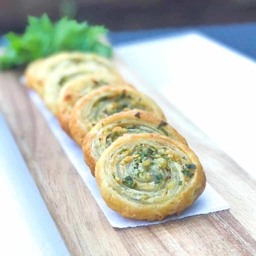 puff pastry pinwheels stacked against each other on board