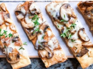 This flatbread appetizer is ideal for parties or entertaining! A simple vegetarian pizza recipe that can be served to any crowd! #flatbread #pizzadough #mushrooms #appetizer
