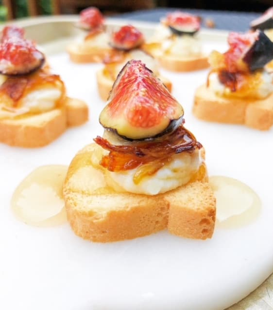 mini toast topped with cheese and a fig drizzled with honey on a plate