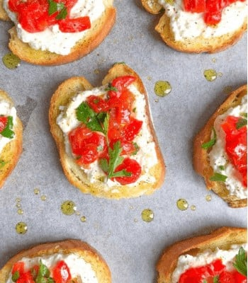roasted peppers on top of toasted bread with ricotta cheese