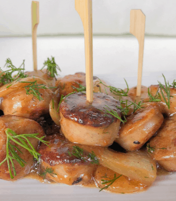 skewered chicken sausages appetizer with dill on top