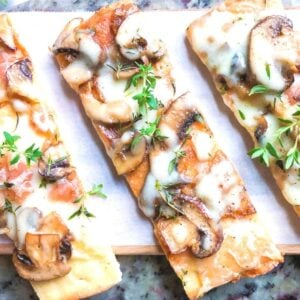 flatbread pizza recipe with mushrooms and onions on cutting board