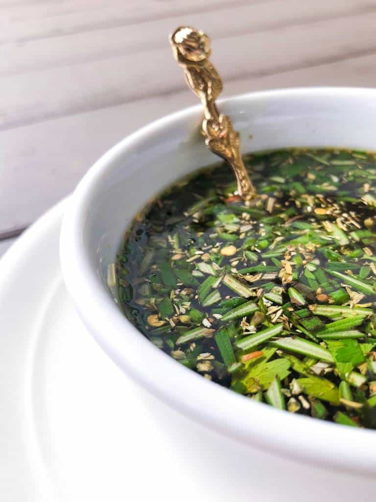 olive oil dip with fresh herbs inside a bowl