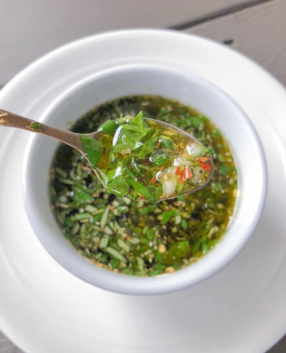 herb infused garlic oil dip in a spoon