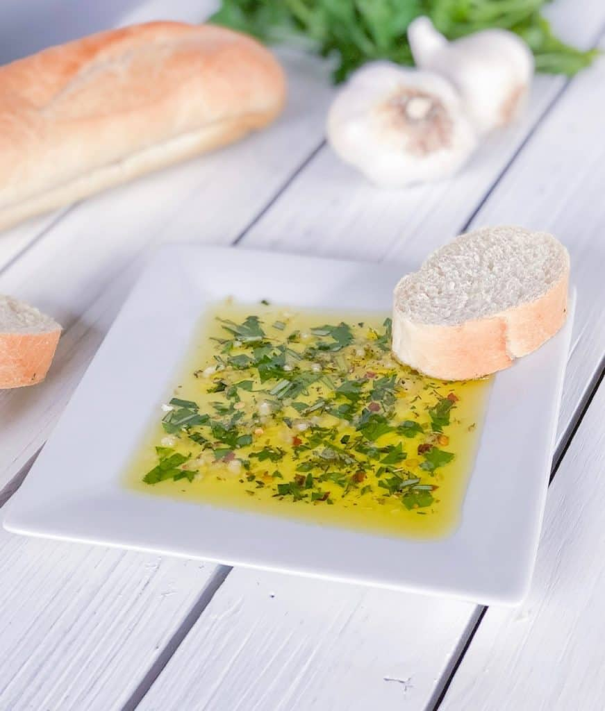 herbs in olive oil on a white plate with a slice of bread next to it
