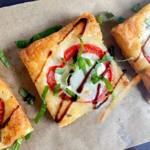 Puff pastry pizza on wooden board with balsamic drizzle.