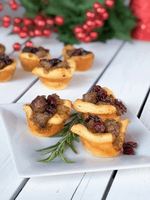 christmas stuffing cups with sausage and craisins on a plate for holiday parties