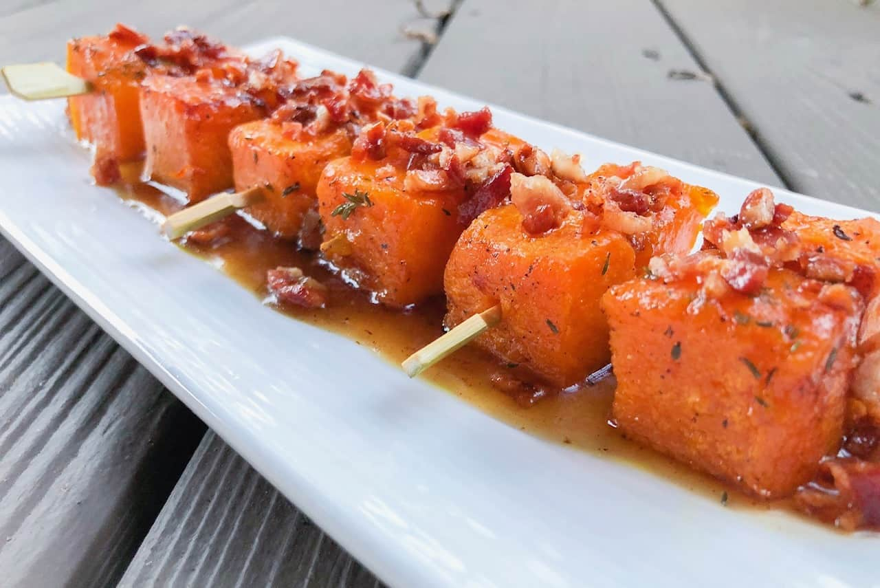 autumn squash skewers on a white plate with bacon crumbles