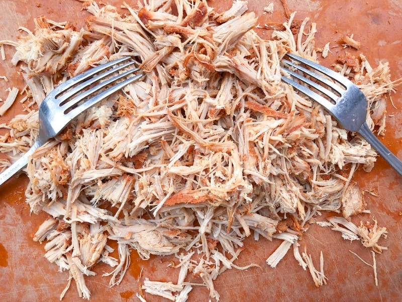pulling pork on a cutting board using two forks