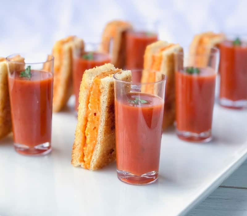 grilled cheese sticks next to tomato soup shooter