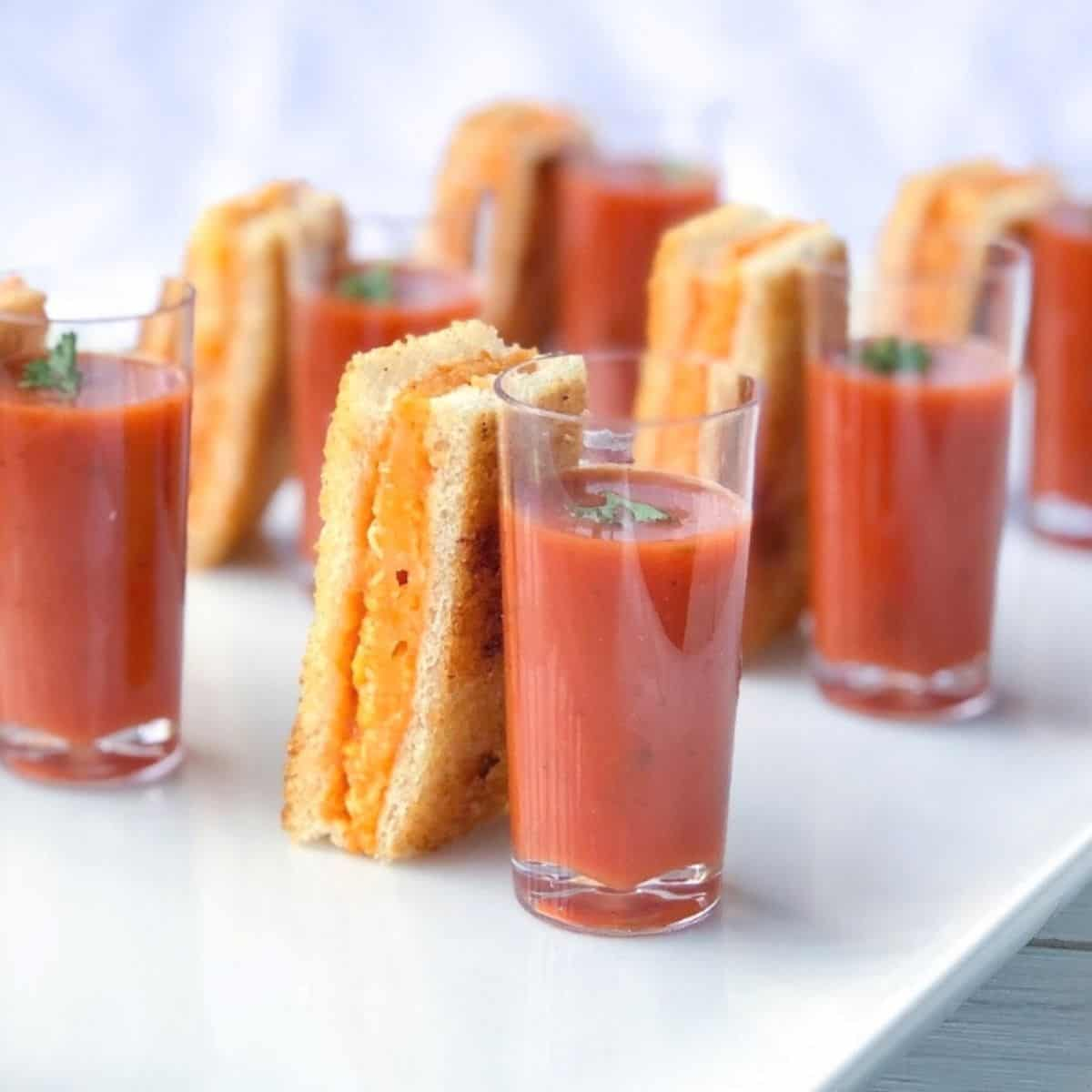 Grilled cheese sticks with tomato soup shooters on a plate.