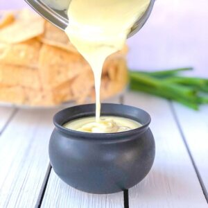 White cheese sauce being poured in a crock.