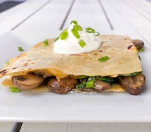 Easy baked mushroom spinach quesadillas! These veggie quesadillas are meatless and can be made for a crowd using a sheet pan in the oven! #quesadillas #ovenbaked #partyfood #fingerfood #cheesy