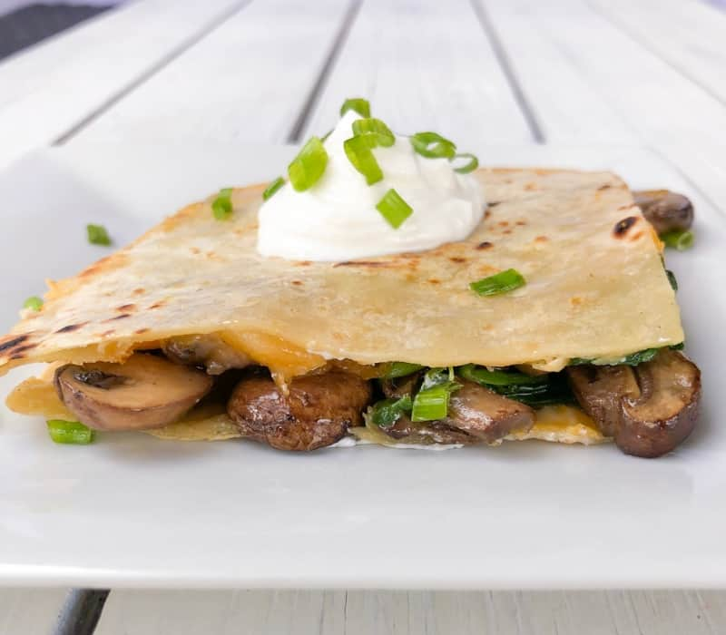 Slice of mushroom quesadilla on a plate topped with sour cream.