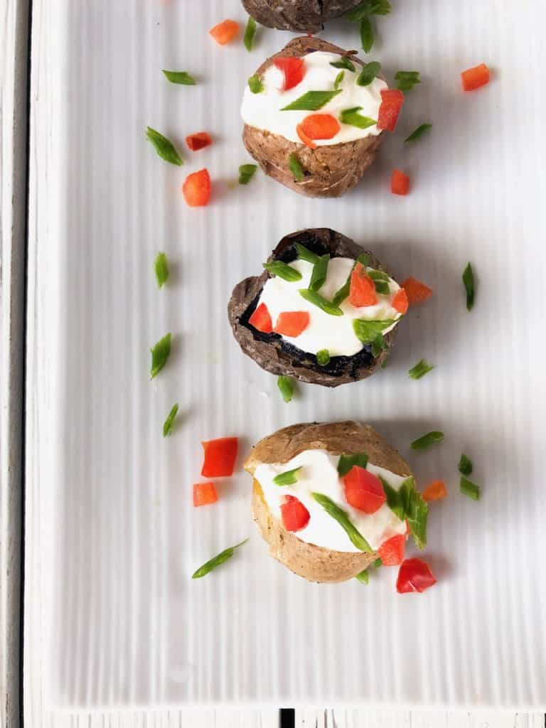 mini baked potato finger food appetizer on a plate.