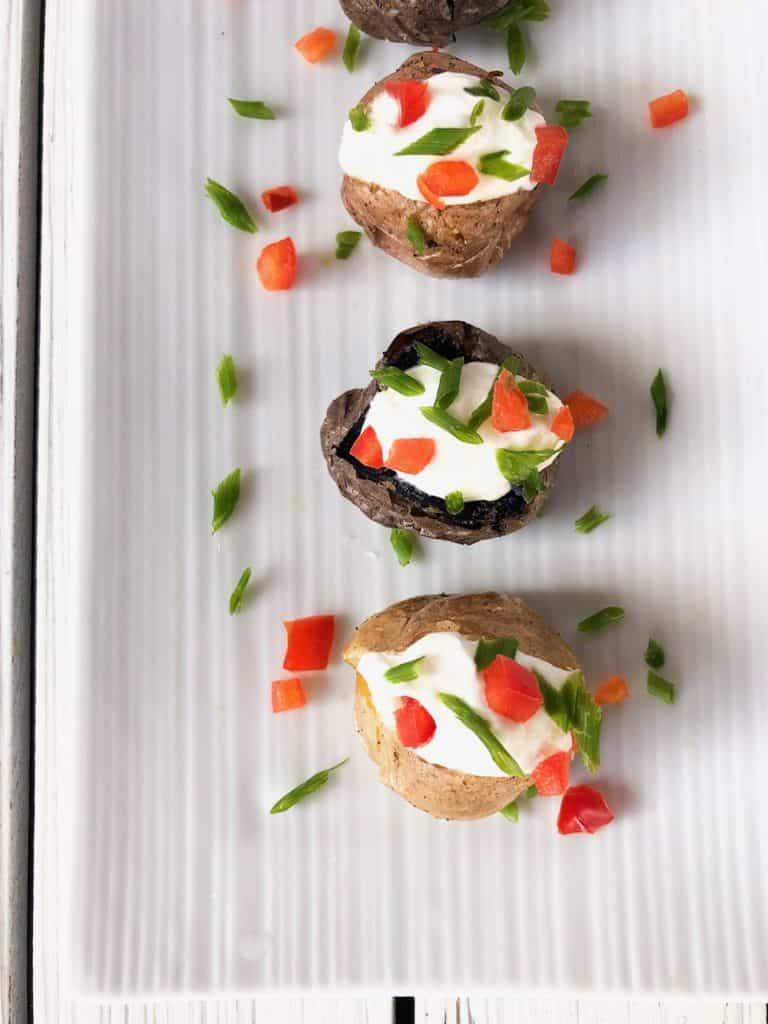 mini baked potato finger food appetizer on a plate.