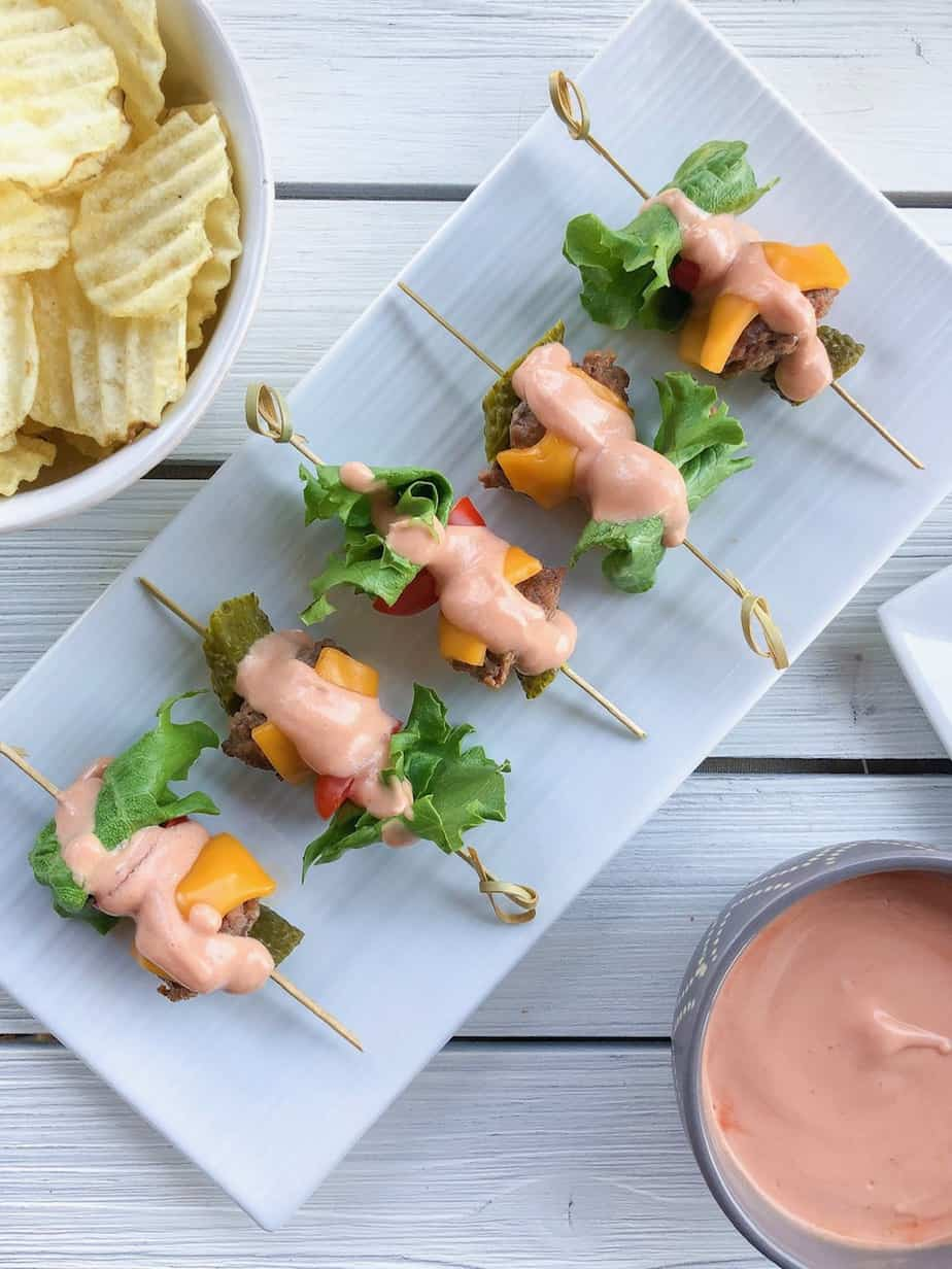 Mini cheeseburger skewers topped with sauce.