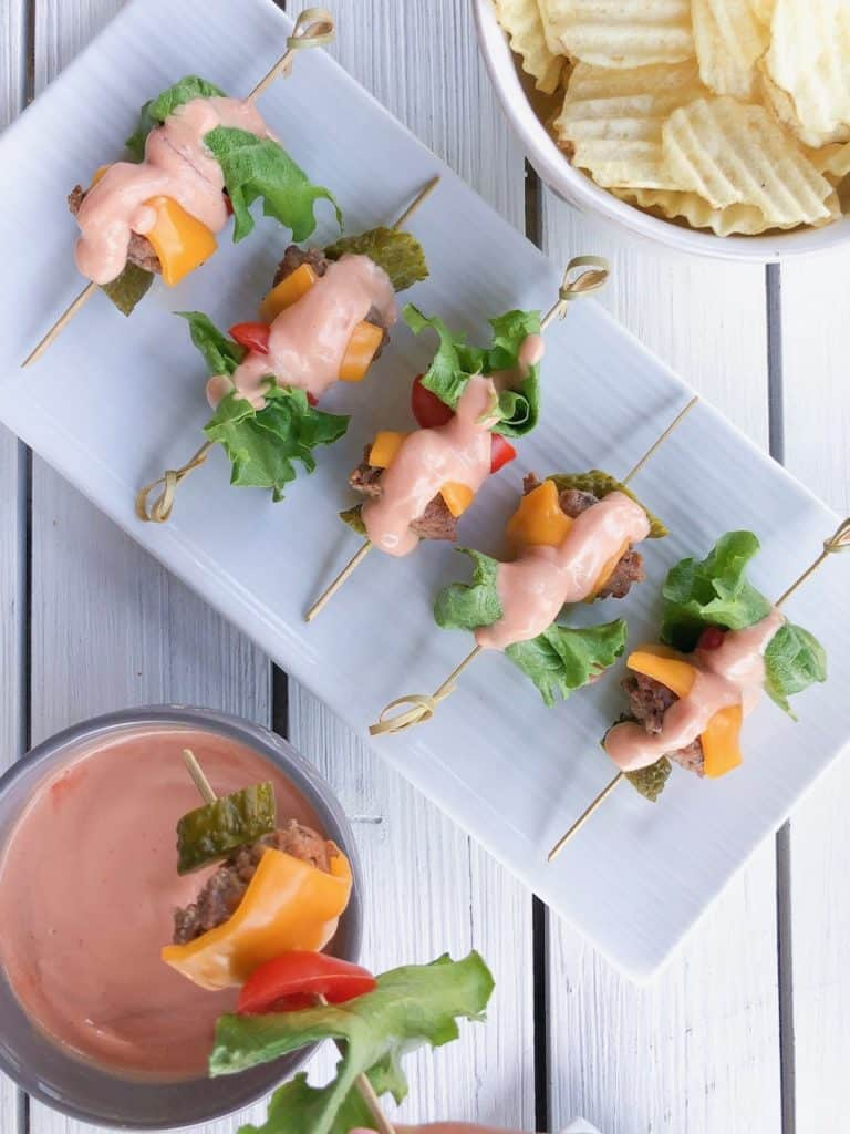 burger skewer bites on a white platter with sauce on top