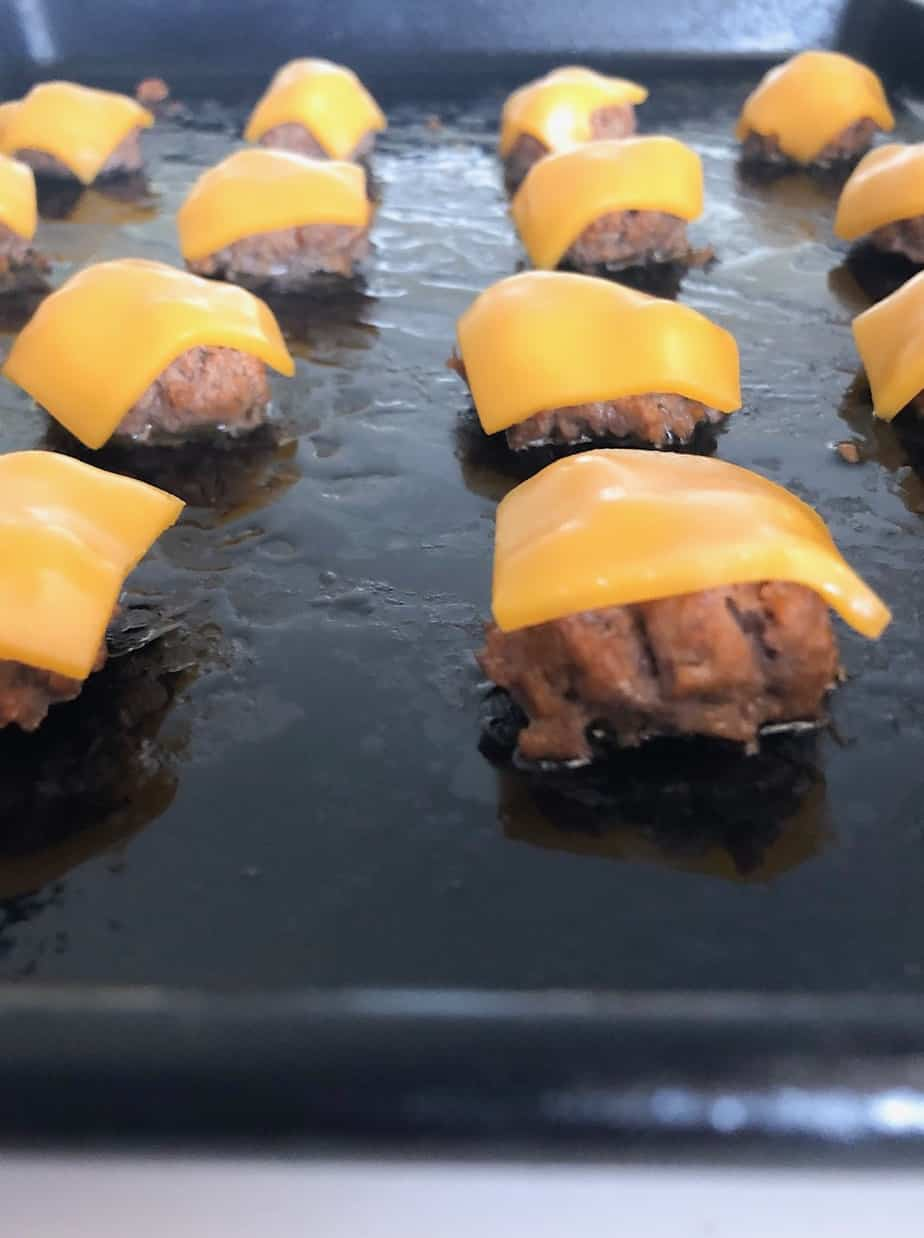 Mini cheeseburger patties on baking sheet.