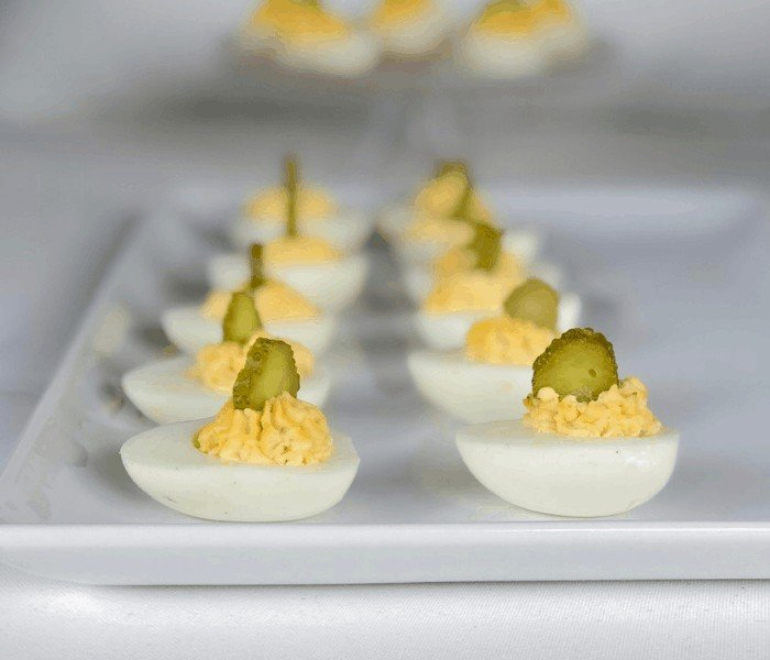 deviled eggs appetizer with pickles on top