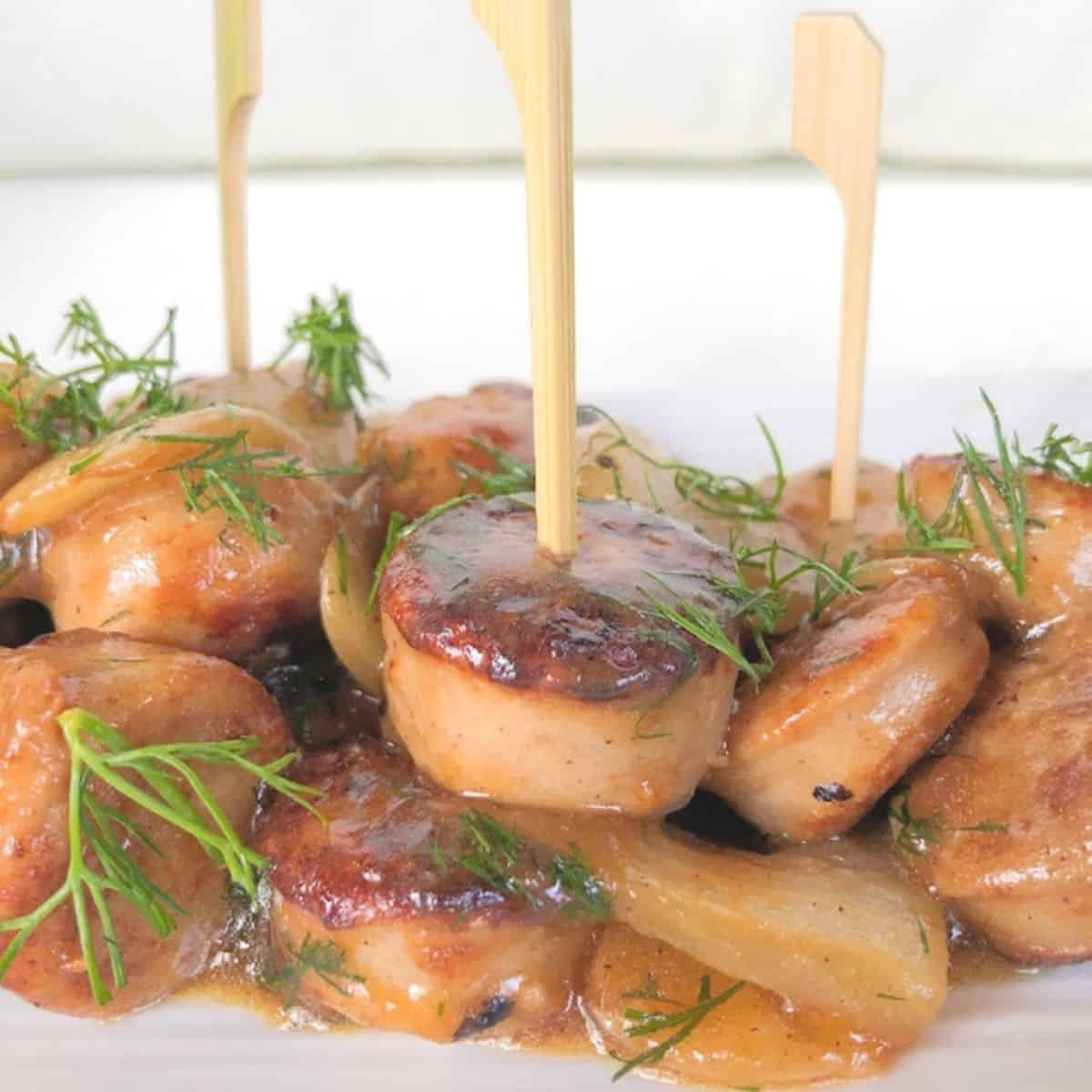 Chicken apple sausage skewered on a plate.