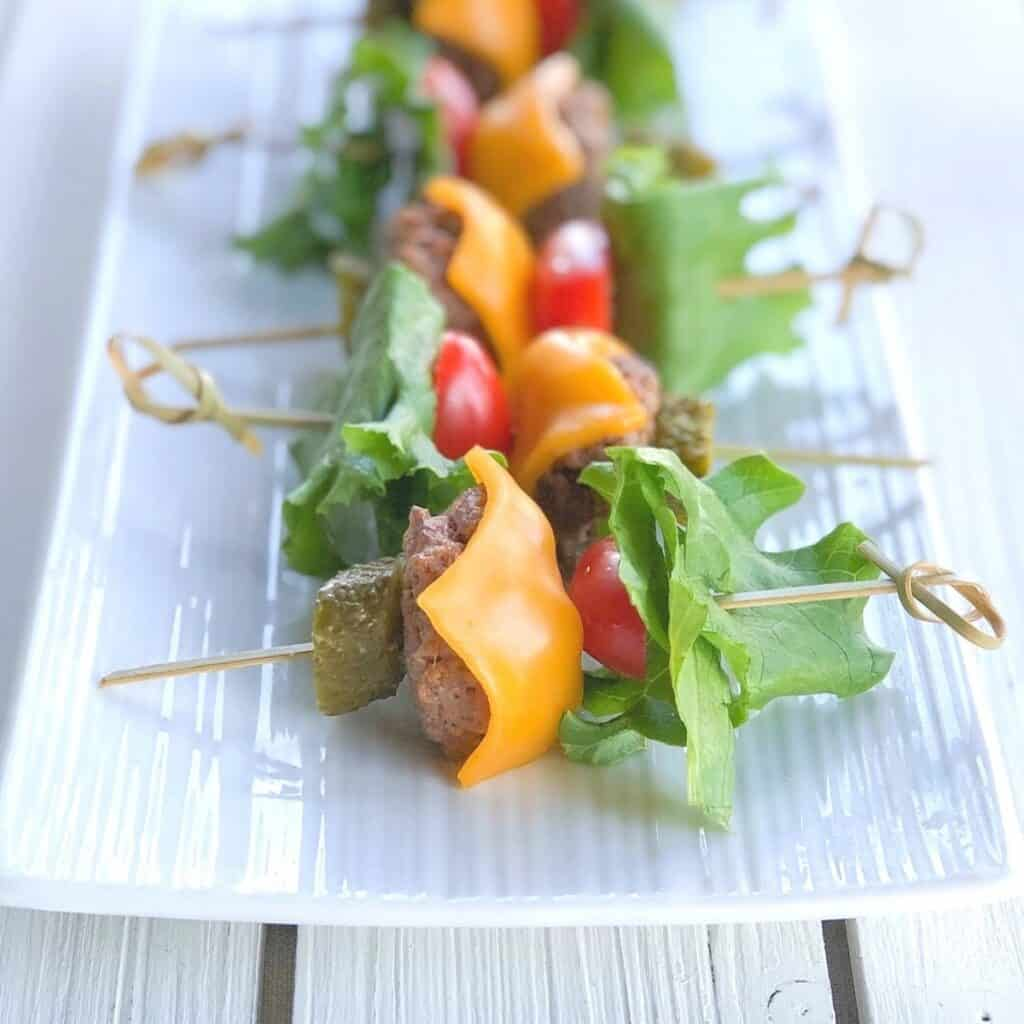 Mini skewered cheeseburger appetizers on a plate.