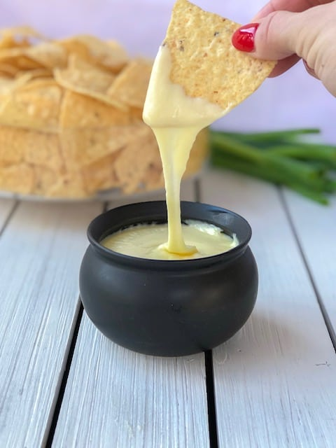 Tortilla chip dipping into cheese sauce.