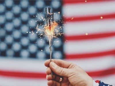 A lit sparkler with the American flag in the background.